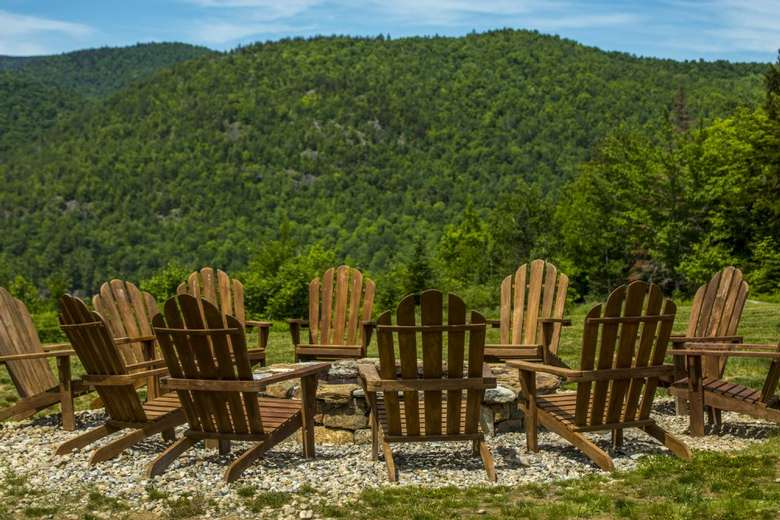 adirondack chairs around fire pit with view of mountains in the back