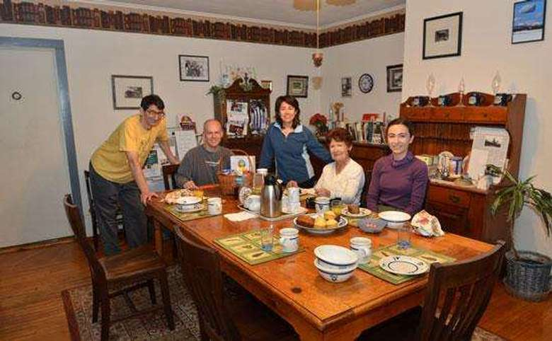 five people gathered around a dining table about to eat breakfast