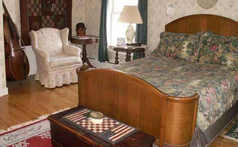 bed with a floral bedspread and a wooden head and footboard