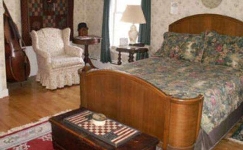 double bed with a floral comforter and a wing-back chair next to it