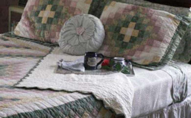 close up of a tea tray on a bed with a patchwoork comforter and shams