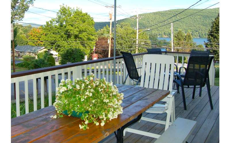 a deck with some patio chairs and tables