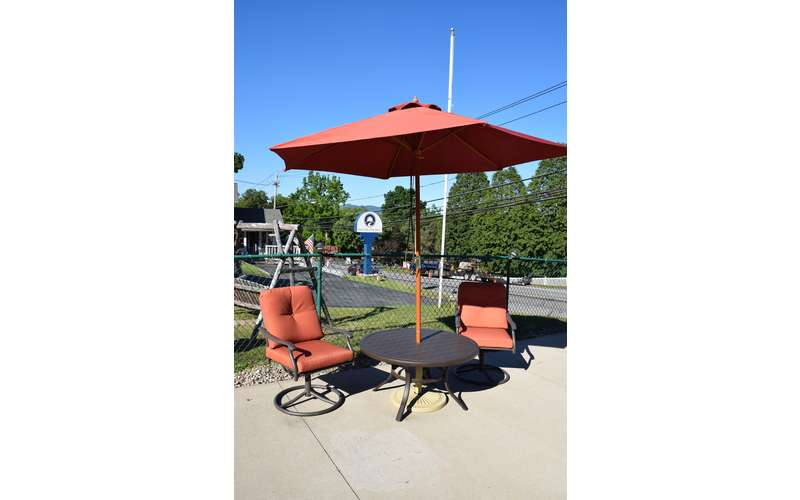 two chairs and a patio table with red umbrella