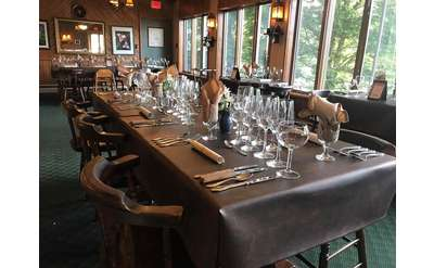 a long dining table with glasses set up on it