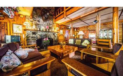 inside of lodge, brightly lit, Adirondack-style, lots of furniture, stone fireplace