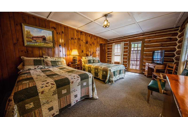 different bedroom with two beds and wood panels
