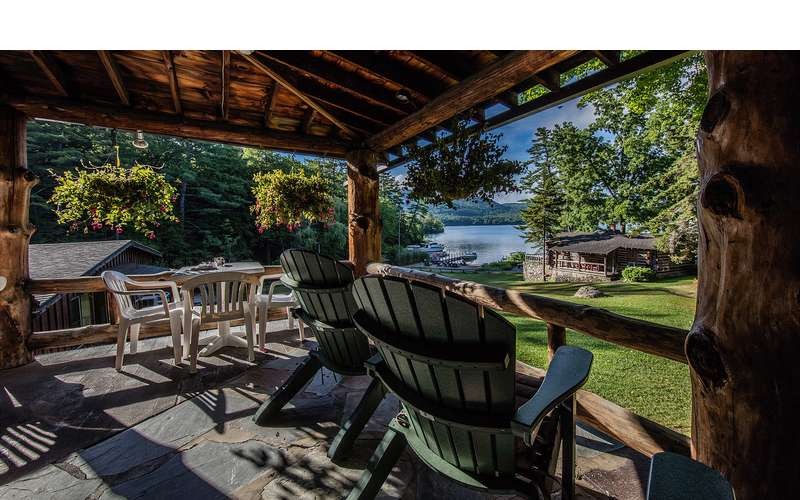 deck with chairs overlooking lake and lawn