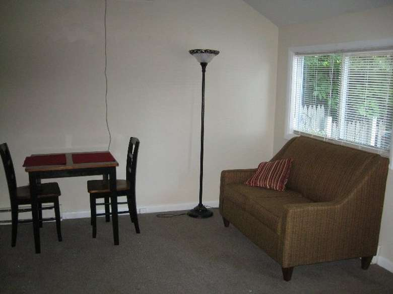 living room area with couch, chairs, table, lamp