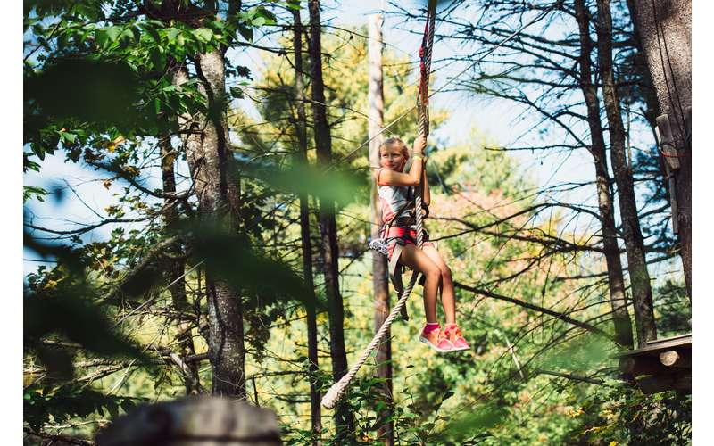a girl hanging onto a zipline