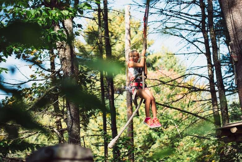 a girl hanging onto a zipline