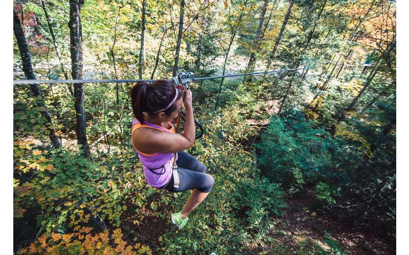 a woman ziplining through the woods
