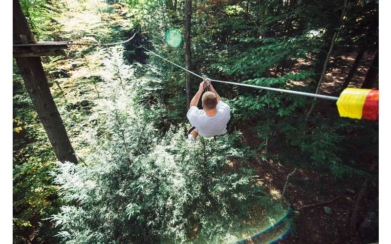 man ziplining through a forest