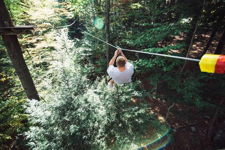 man ziplining through a forest