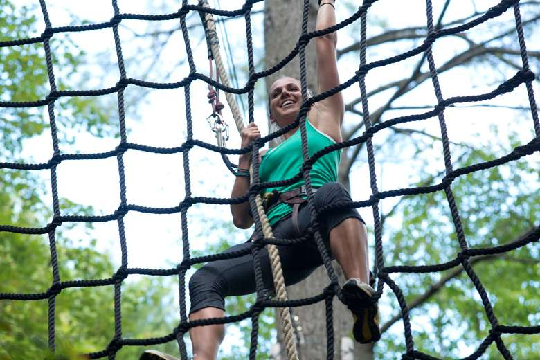 a woman climbing up a large rope net