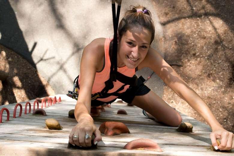 a woman climbing up a wall