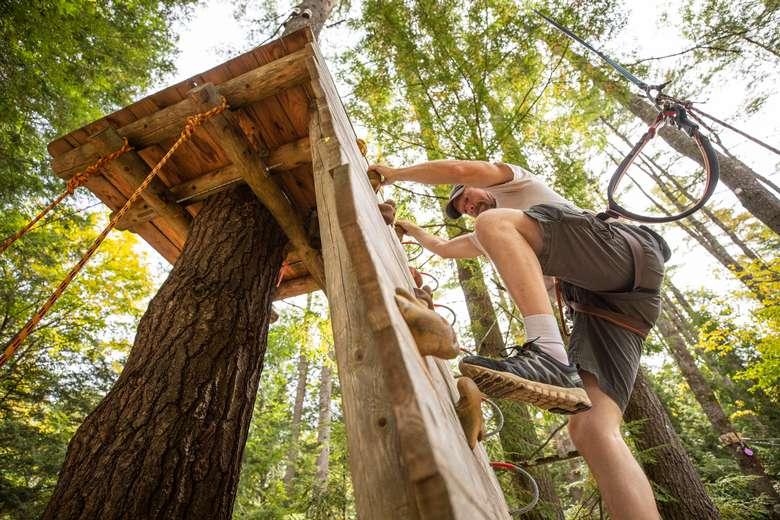 Man climbing up a rock wall obstacle at Adirondack Extreme