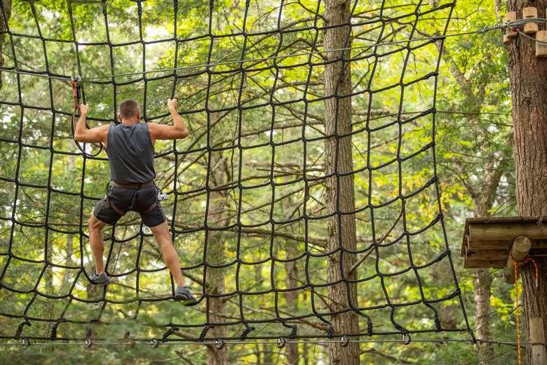 Man climbing large cargo net at Adirondack Extreme