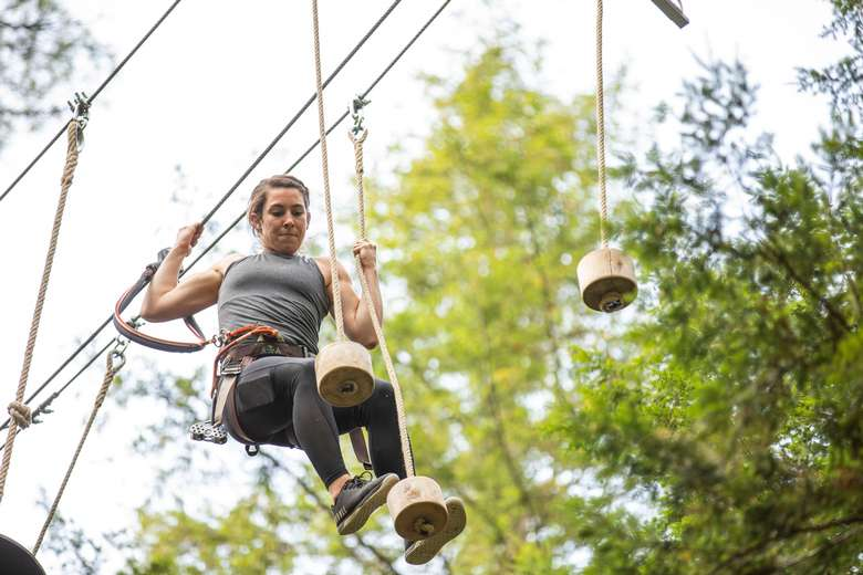 Woman on mini pogo logs obstacle at Adirondack Extreme