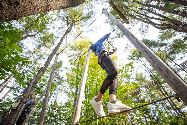 Girl on a tight rope obstacle at Adirondack Extreme