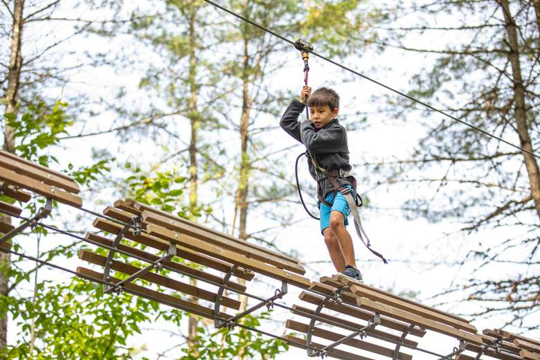 Young boy on the Kids Course ages 6+ barrel obstacle at Adirondack Extreme