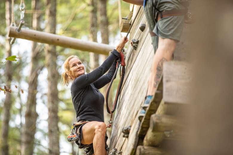 Woman climbing a rock wall obstacle at Adirondack Extreme
