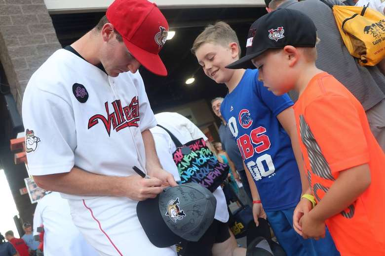 baseball player signing hat for kids