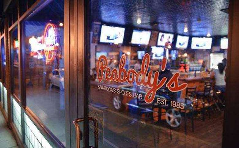 peabody's logo on the door of their bar with televisions visible in the background