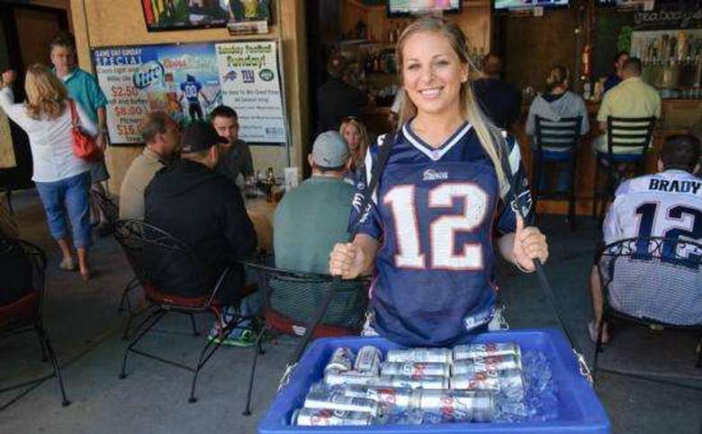 waitress in a tom brady jersey carrying a bucket of beer