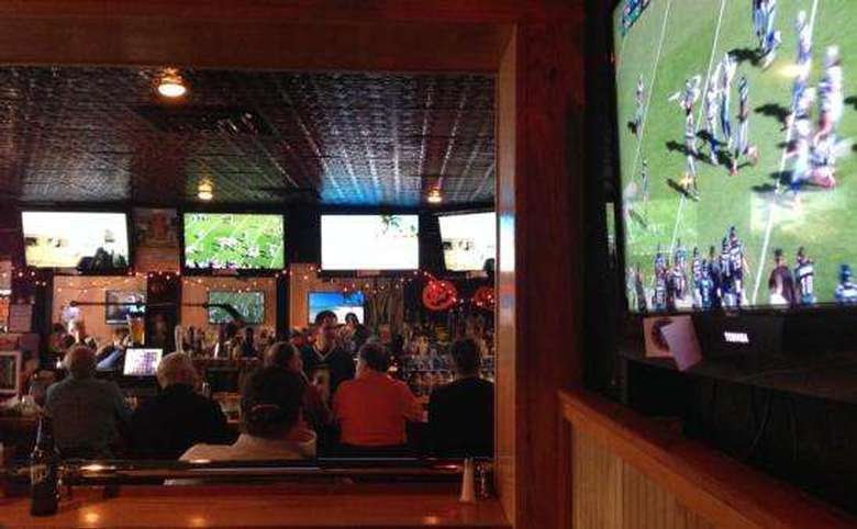 football on a large tv with other tvs and bar patrons visible in the background