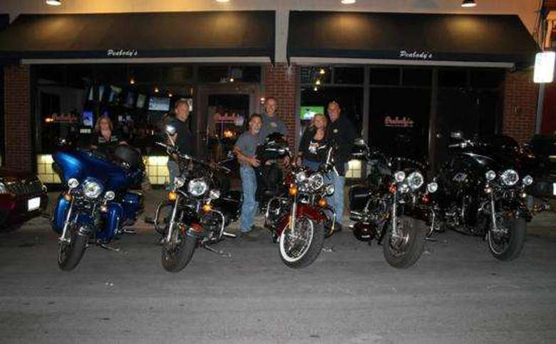 row of parked motorcycles and a group of bikers