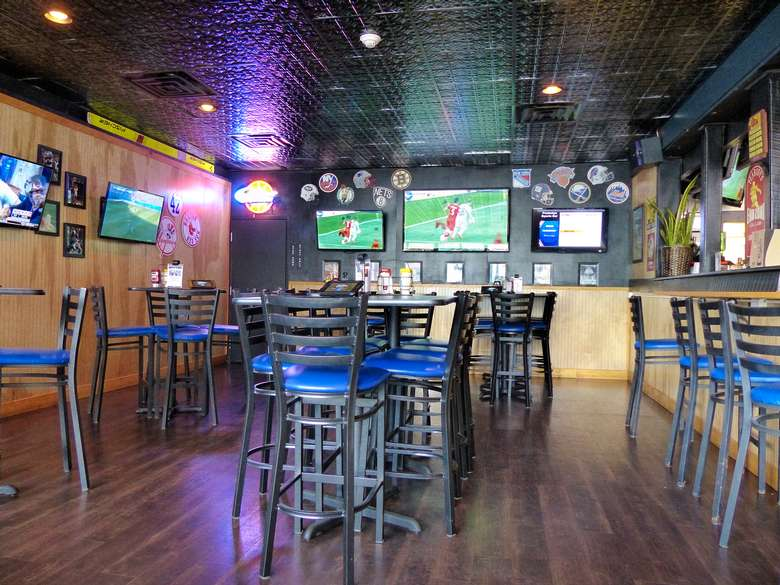 high top tables with several tvs on the walls