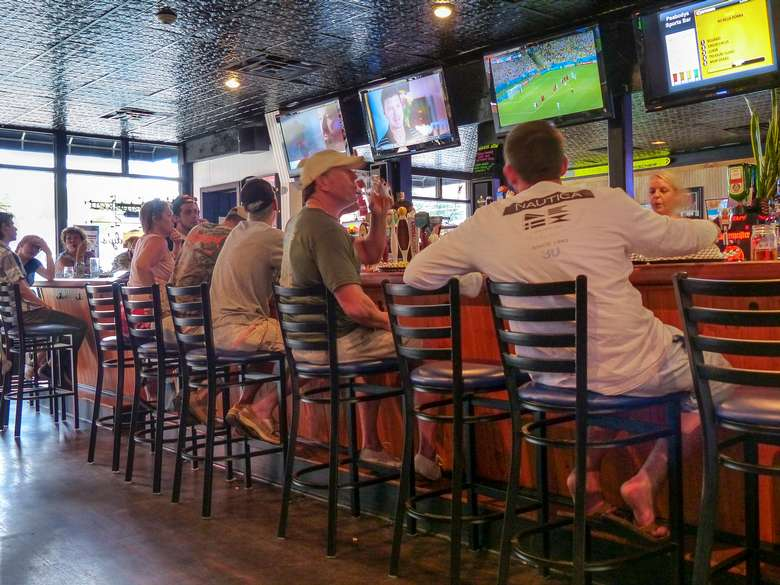 people sitting at the bar watching sports on tv