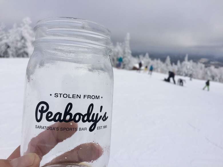 person holding a mason jar that says stolen from peabody's on a ski mountain