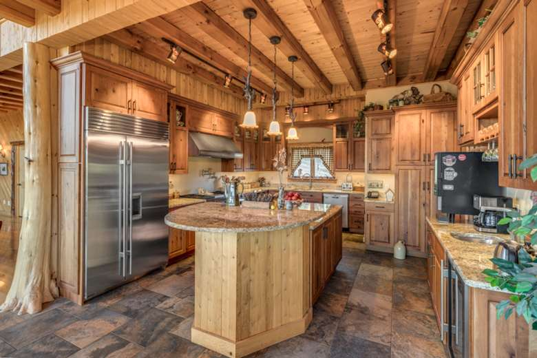 kitchen in a log house with wooden floors, ceilings, cabinets, and rustic accents