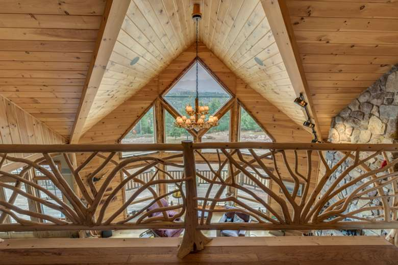 interior of a log home as seen from behind a decorative wooden railing