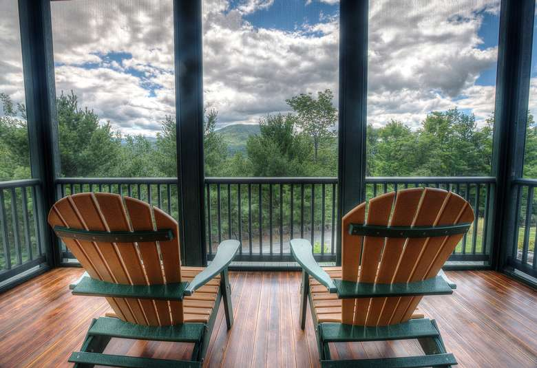 two adirondack chairs on a screened in porch overlooking nature