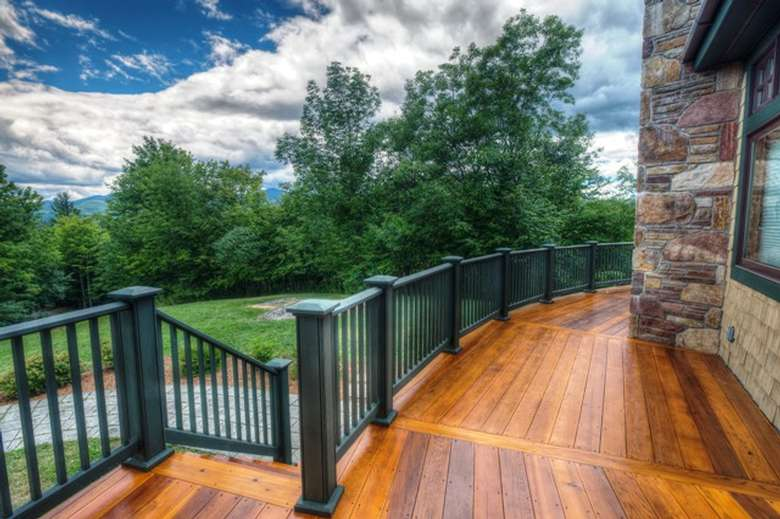 wooden wrap-around deck overlooking a wooded area