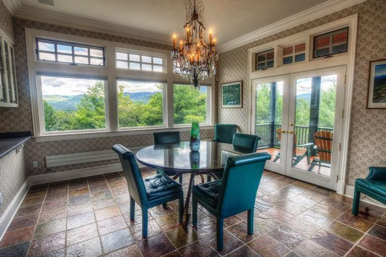 small round dining table with four blue chairs and windows looking out onto a wooded area