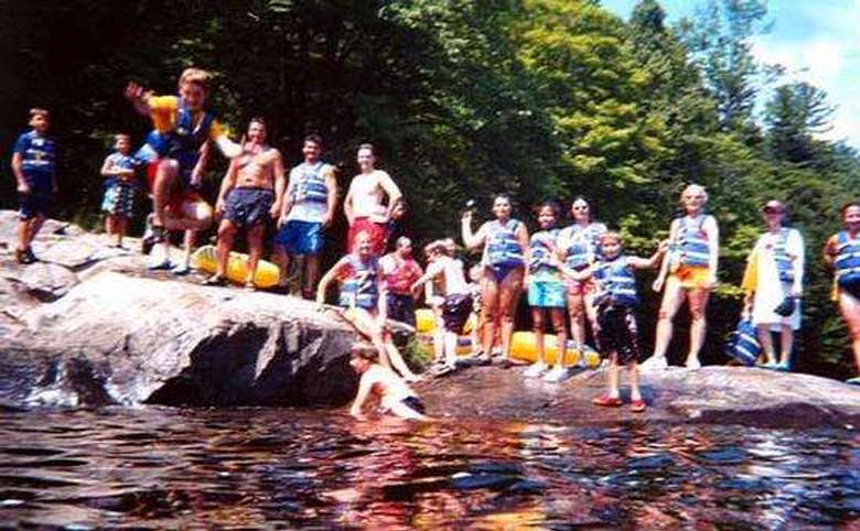 group of kids wearing life jackets taking turns jumping off a rock into the river