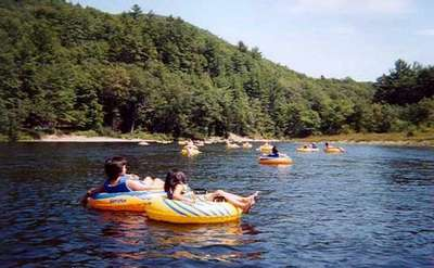 people floating down a calm river in yellow and blue inner tubes on a sunny day