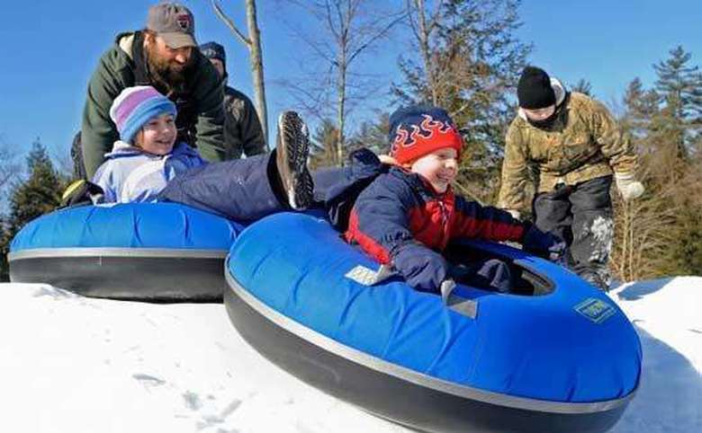 two kids in blue tubes starting down a hill in the winter