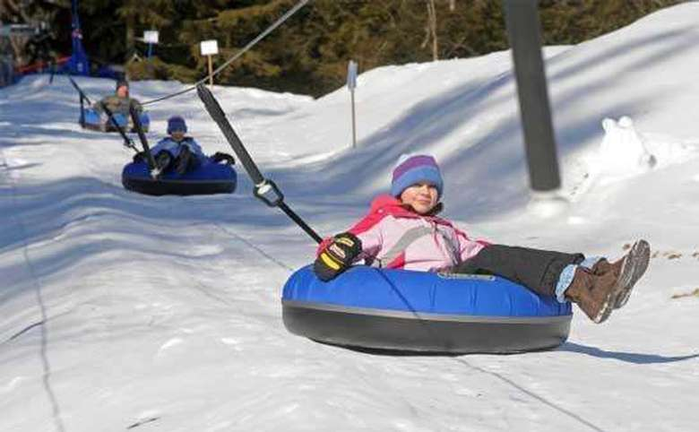 a tubing lift pulling kids up a hill while they lay in blue inner tubes