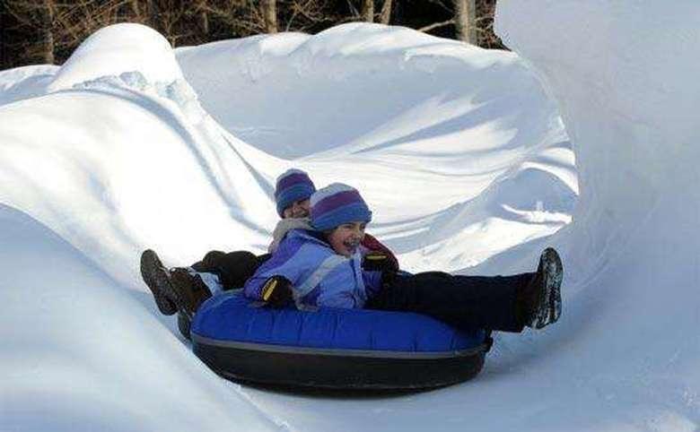 two kids snow tubing in blue inner tubes