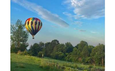 a colorful hot air balloon in the sky above a field