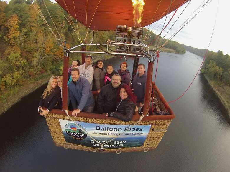 hot air balloon with people over a river