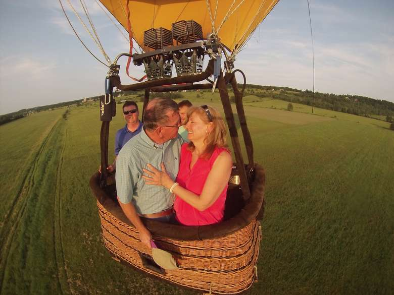 man and woman close together in a hot air balloon basket