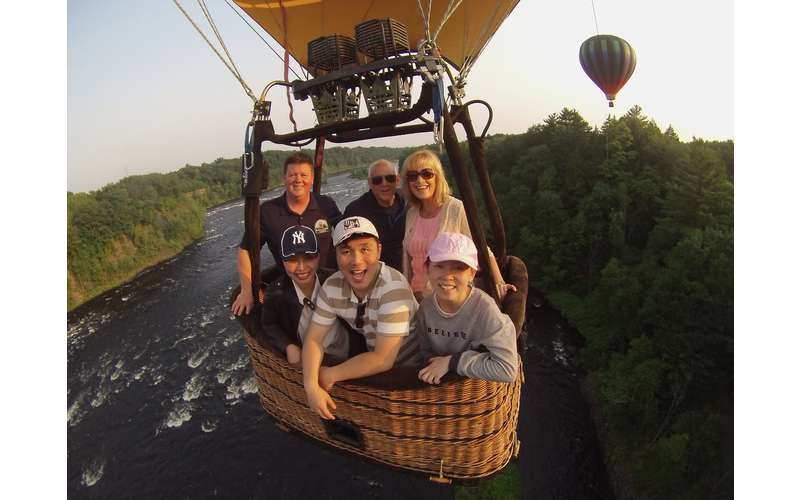 people in a hot air balloon flying over a river