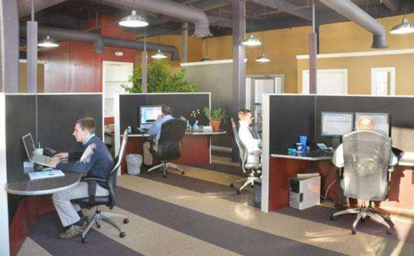 an office space with cubicles and people working at computers