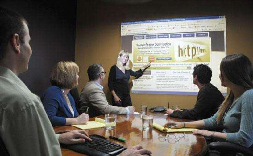 a woman pointing at a projector screen in a small conference room with people