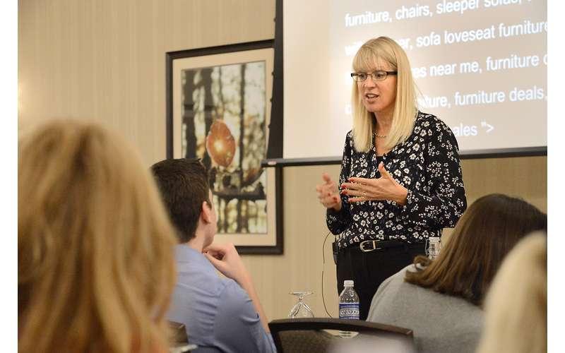 a woman speaking near a projector screen